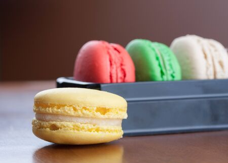 Close-up on yellow macaroons with red, green and beige macarons cakes on background Reklamní fotografie