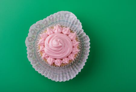 Delicious sweet vanilla cupcake with pink icing sugar, green background Reklamní fotografie