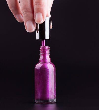 Female hand opening a bottle of purple nail polish