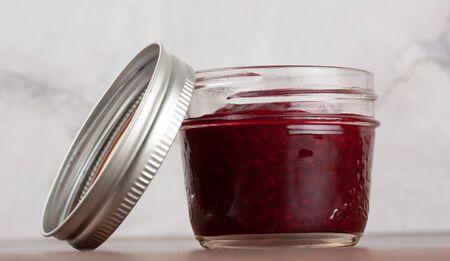Delicious homemade raspberry jam in a reusable glass jar