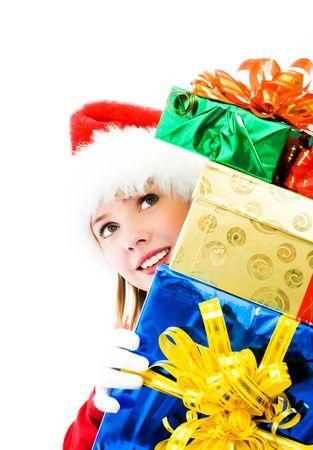 pretty girl dressed as Santa hiding behind the Christmas presents photo