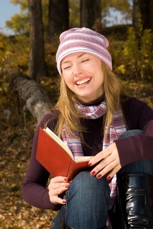 laughing girl reads a book in the park photo