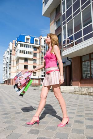 suny: happy girl with shopping bags walking outdoor Stock Photo