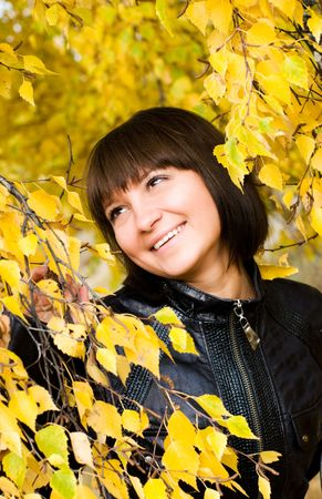 careless: cheerful cute girl in the park looking at yellow leaves