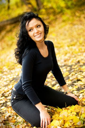 pretty brunette girl sitting on the grass covered with yellow leaves Stock Photo - 3784067
