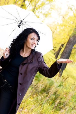 happy girl with an umbrella in the park checks if it is raining photo