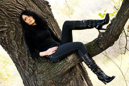 melancholic: beautiful melancholic girl sitting on the tree