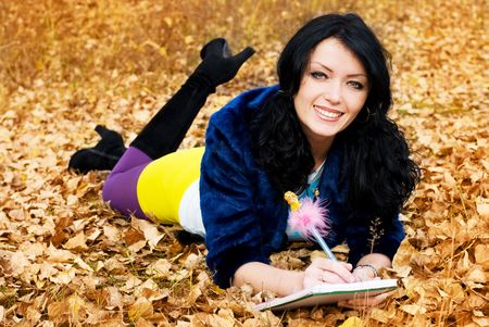 pretty brunette girl in the park with a pen and a note-book photo