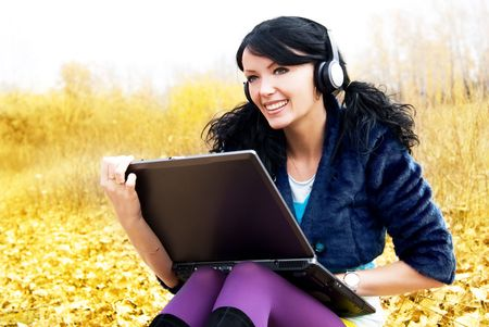 pretty brunette woman with a laptop in the park photo