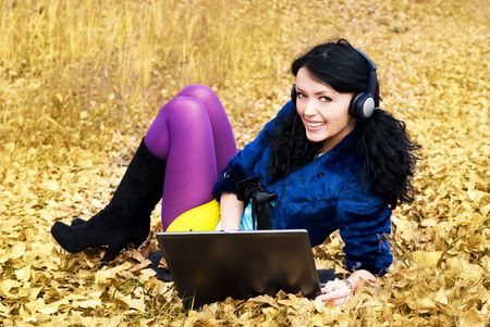 pretty smiling girl with a laptop outdoor photo