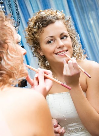pretty smiling bride paints her lips near the mirror photo