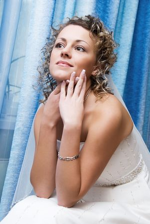 pretty young bride sitting on the bed photo