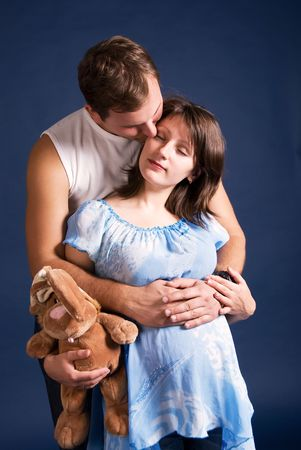 pregnant woman and her husband embracing isolated against blue background photo