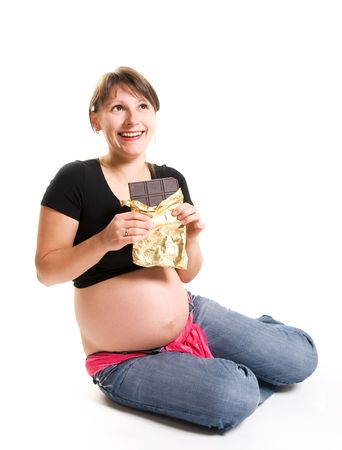 happy pregnant woman eating chocolate isolated against white background photo