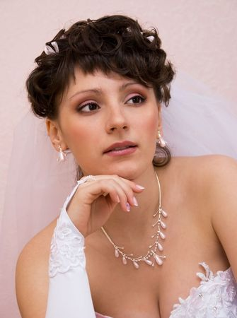 portrait of a thoughtful bride sitting at home alone photo