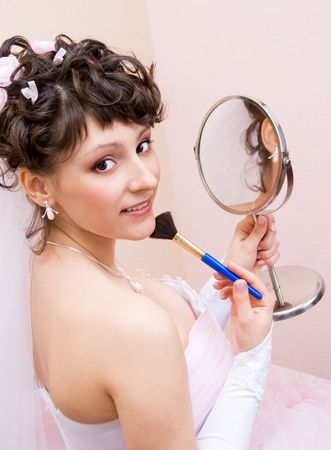 portrait of a lovely young bride with a mirror and a brush photo