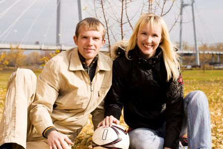 happy young couple with a football ball outdoor photo
