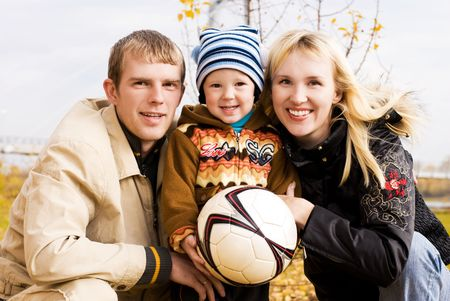 happy smiling family with a football ball outdoor photo