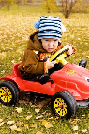 funny serious boy driving a car in the park