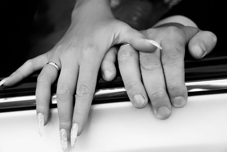 black and white picture of the hands of a bride and a groom on the car window photo