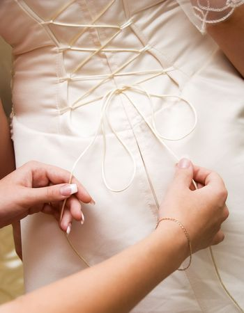 get dressed: young woman tightening the courset of a bride