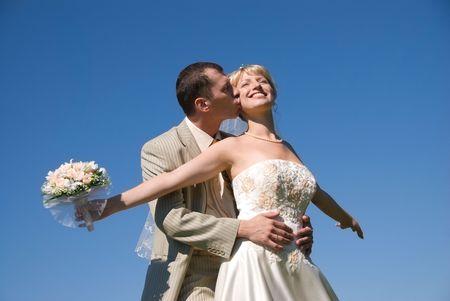 besos apasionados: feliz novia y el novio en contra de cielo azul