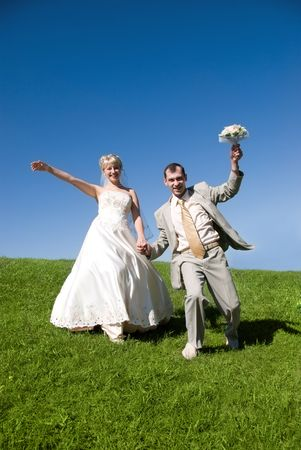 bride and groom are having fun on the hill photo