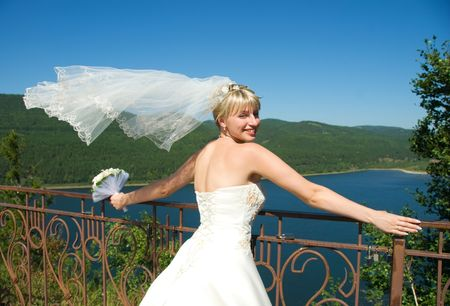 pretty young bride with a flying veil outdoor photo