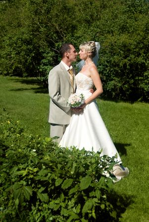 happy bride and groom embrace in the park photo
