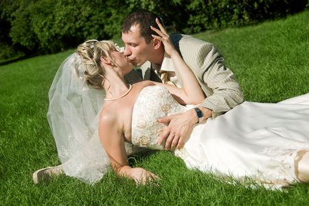 bride and groom kissing in the park on the grass photo