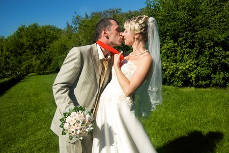 young bride and groom kissing in the park photo
