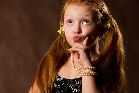 capricious: cute capritious little girl against brown background