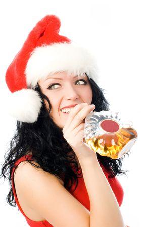 beautiful smiling brunette woman wearing Santas hat drinking cognac photo