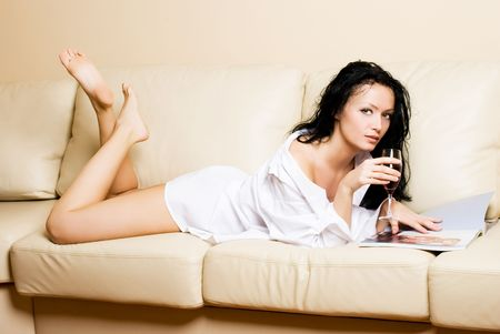 beautiful brunette woman relaxing on the sofa with the magazine and a glass of juice photo