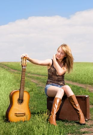 beautiful blond girl with a guitar and old suitcase outdoor on the road photo
