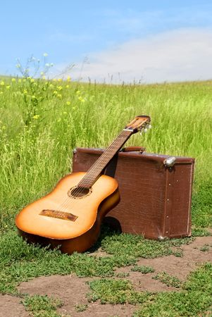 leathern: guitar and old leathern suitcase outdoor on the road Stock Photo