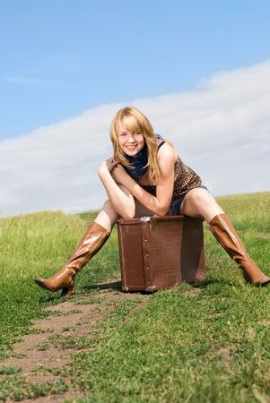 leathern: beautiful young blond woman outdoor on the road with a guitar and an old leathern suitcase Stock Photo