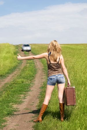 beautiful young blond woman outdoor on the road with a guitar and an old leathern suitcase photo