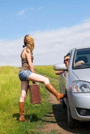 leathern: beautiful young blond woman outdoor on the road with a guitar and an old leathern suitcase persuades a man to give her a lift Stock Photo