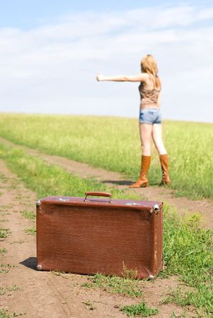 attractive young blond woman with an old leathern suitcase outdoor on the road photo