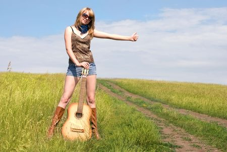 attractive young blond woman with a guitar outdoor on the road trying to stop a car photo