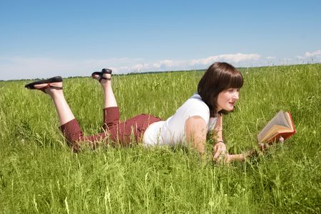 poems: pretty brunette girl lies on the grass and reads a book outdoor Stock Photo