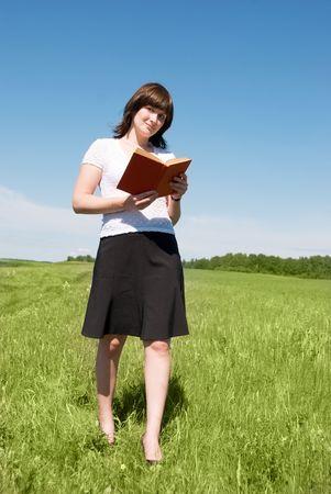 slowly: atractiva morena niña caminando con un libro al aire libre en verano