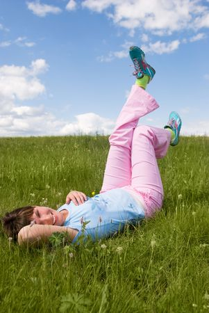 happy beautiful young woman on the grass on the hill in summer photo