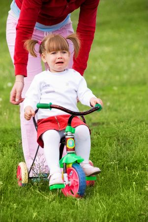unsatisfied: cute scared two year old girl unwilling to learn riding a bysicle