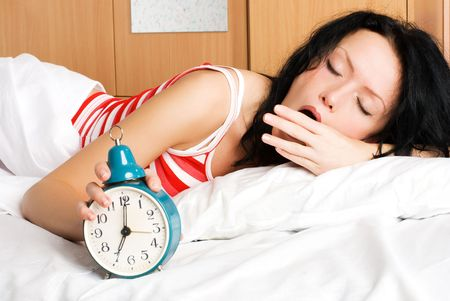 young beautiful brunette woman waking up, switching off the alarm-clock and yawning in the morning photo