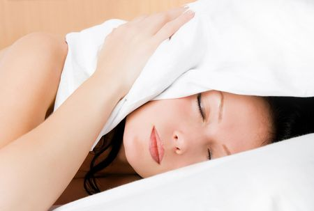 young attractive brunette woman sleeping in her bed and covering her heat with a pillow Stock Photo - 3910164