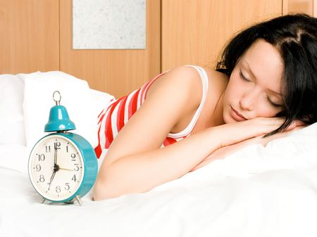 pretty young brunette woman sleeping with an alarm clock standing near her photo
