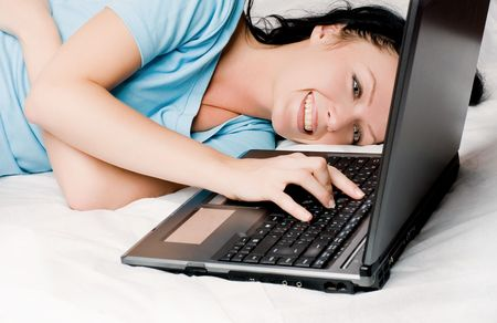 cheerful beautiful young brunette woman with a laptop on the bed photo