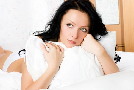 hesitations: beautiful thoughtful brunette woman with a pillow on the bed Stock Photo